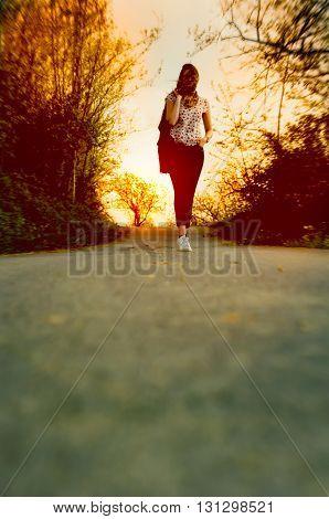Young Woman Walking Alone Enjoying Warm Evening During Sunset