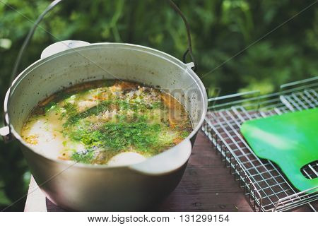cauldron with fish soup on the table