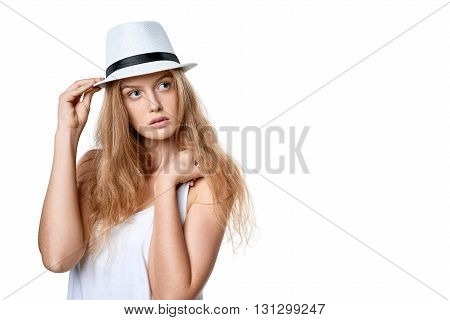 Closeup of beautiful slytish woman posing in fedora hat looking away at blank copy space, over white background