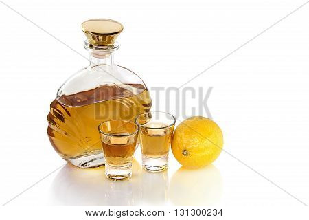 Bottle with two shot glasses of tequila and lemon on a white background