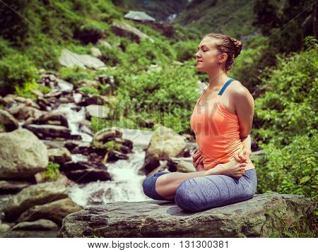 Vintage retro effect hipster style image of sporty fit woman doing yoga - meditating in Baddha Padmasana (Bound Lotus Pose) outdoors at tropical waterfall