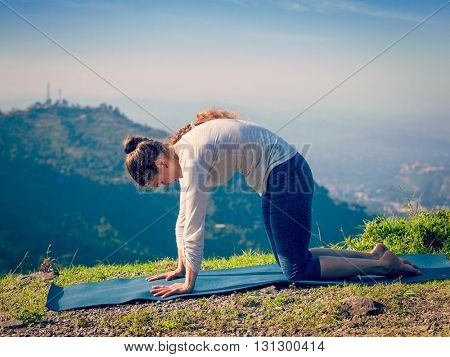 Vintage retro effect hipster style image of sporty fit woman practices yoga asana Marjariasana - cat pose outdoors in Himalayas