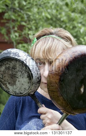 Woman holding two frying pans while standing in a garden outdoor vertical shot with blurred background