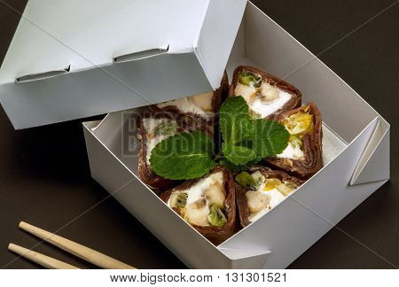 Sweet roll in a box for transportation. Chocolate pancake , cream cheese , apple, banana