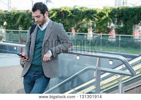 urban man calling on the phone near a metro station