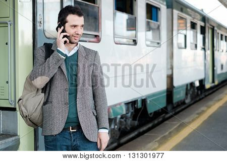 standing man calling on the phone waiting for the train in a train station platform