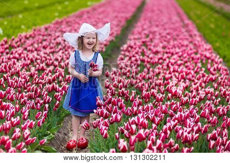 Adorable little girl wearing Dutch traditional national costume dress wooden clogs and hat playing in a field of blooming tulips next to a windmill in Amsterdam region Holland Netherlands