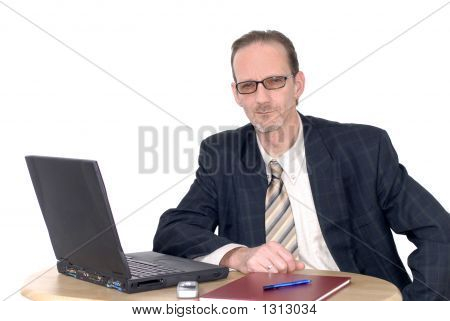 Pensive Looking Businessman Working On Laptop