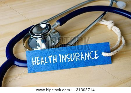Medical Conceptual Image With Heatlh Insurance Words And Stethoscope On Wooden Background.