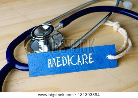 Medical Conceptual Image With Medicare Words And Stethoscope On Wooden Background.