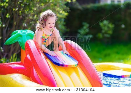 Children playing in inflatable baby pool. Kids swim and splash in colorful garden play center. Happy little girl playing with water toys on hot summer day. Family having fun outdoors in the backyard.
