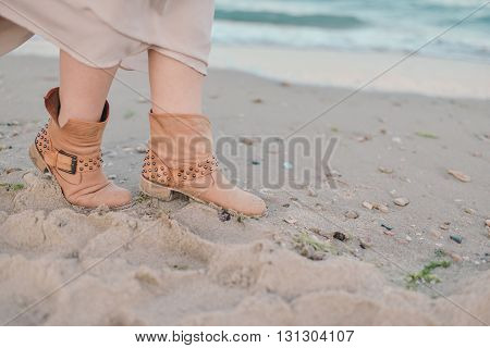 the sea on the sand female legs in brown suede boots