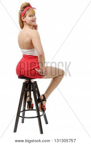 beautiful girl in red shorts sitting on a stool isolated on white background