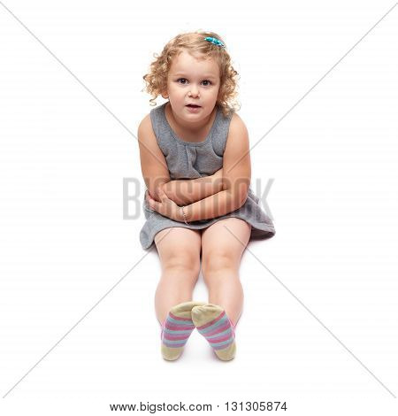 Young little girl with curly hair in gray dress sitting over isolated white background