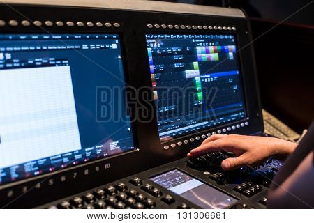 Large modern show light controller with screens and operators hand and ajusted presets - close up photo