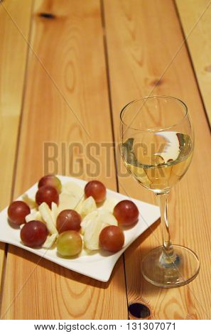Close up photo of white wine glass and grapes with cheese on wooden table
