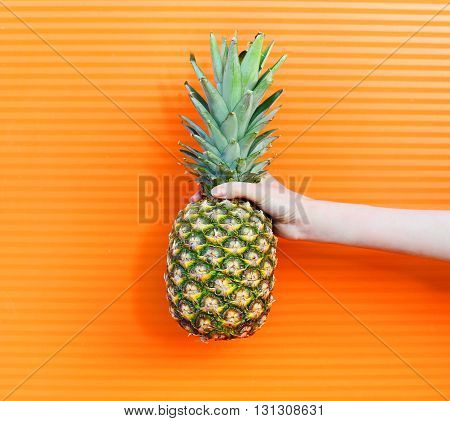 Hand And Fruit Pineapple Over Colorful Orange Background