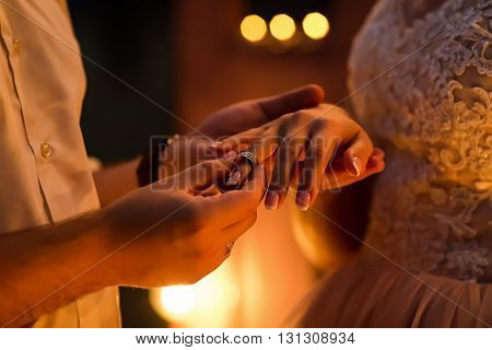 Wedding ceremony. The groom wears a wedding ring on the finger of the bride on a background of the evening lights close-up