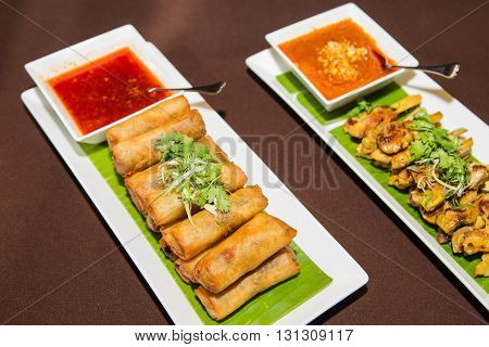 Vegetables spring roll and chicken satay barbecue and sauce on white plate.