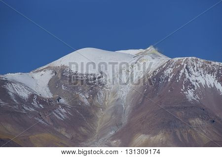 Snow covered peak of the active Guallatiri volcano (6063 m) towering above the Altiplano and cliffs running along the valley of the River Lauca in Lauca National Park, northern Chile.