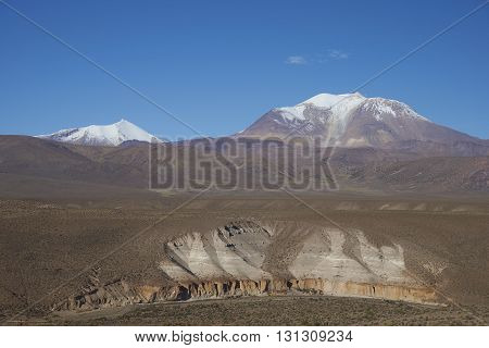 Snow covered Guallatiri volcano (6063 m) towering above the Altiplano and cliffs running along the valley of the River Lauca in Lauca National Park, northern Chile.