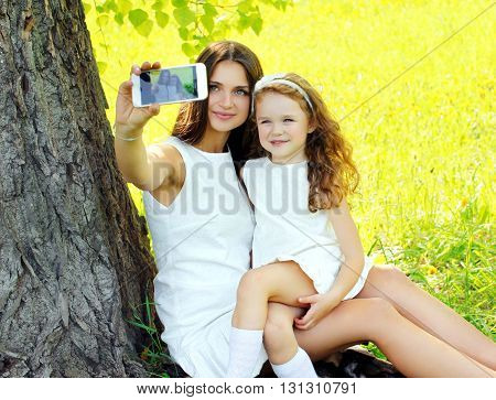 Mother And Daughter Child Taking Selfie Portrait On Smartphone Outdoors Summer