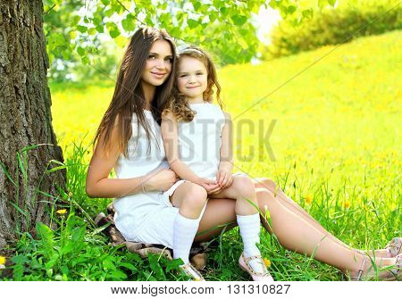 Mother And Daughter Child Together Sitting On Grass Near Tree In Summer Day
