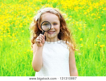 Portrait Little Girl Looking Through Magnifying Glass On Summer Floral Yellow Dandelions Field