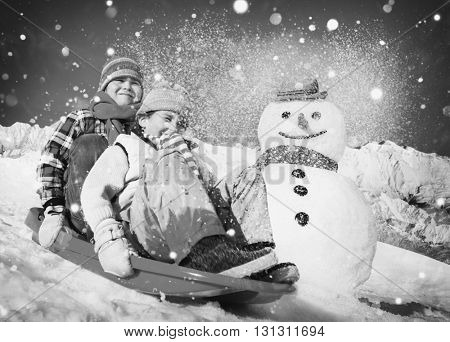 Little Girl and Boy Outdoors Sleding and Snowman Concept