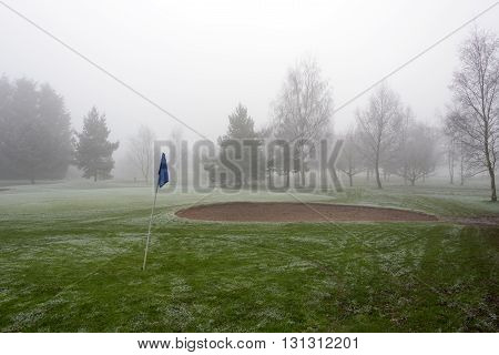 Sand bunker on an empty golf course on a cold and foggy day