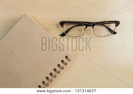 Brown notebook with eyeglasses on wood background under window light