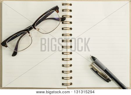 Black pen and notebook with eyeglasses on wood background under window light