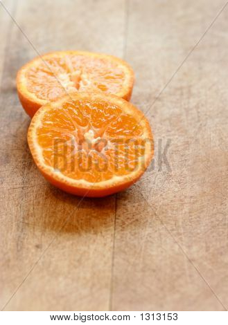 Two Slices Of Oranges On Chopping Board