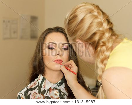 Woman stylist does a make-up to the beautiful girl