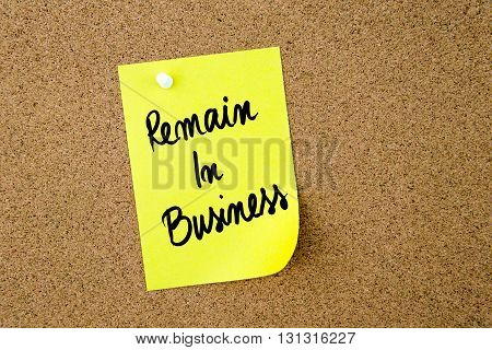 Remain In Business Written On Yellow Paper Note