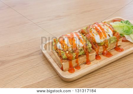benedict egg on piece of bread with kiwi sauce on the wooden table