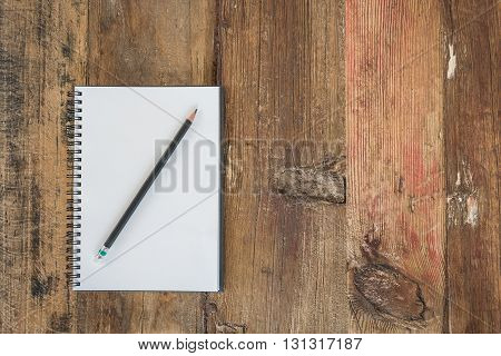 black pencil on white notebook with wooden background