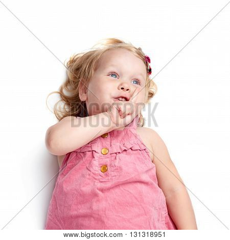 Young little girl with curly hair in pink dress lying and doing shh silence sign over isolated white background