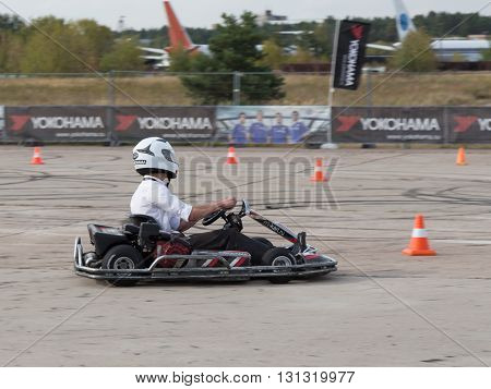 Moscow - August 28 2015: A man in a white hat and white shirt riding on the race cart on the racetrack August 28 2015 Moscow Russia