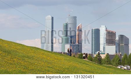 Moscow - May 6 2016: The complex of tall skyscrapers Moscow City a beautiful view from the Poklonnaya Hill and people walk in Victory Park May 6 2016 Moscow Russia