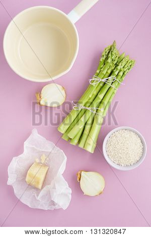 Ingredients for making green asparagus risotto on pink surface