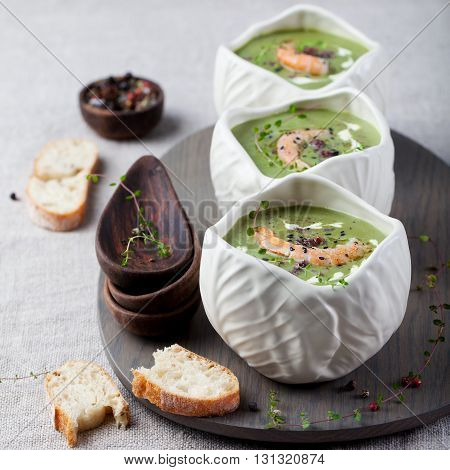 Broccoli, spinach cream soup with shrimp in a white bowls on a wooden board Top view