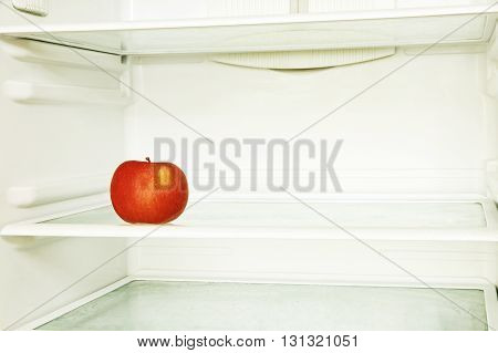 Red single apple in domestic refrigerator taken closeup. Toned image.