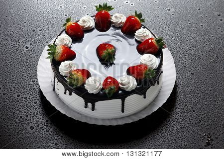 Strawberry birthday cake with whipped cream and chocolate