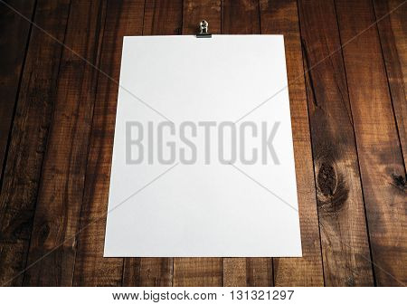 Photo of blank white paper poster on vintage wooden table background. Blank sheet of paper with plenty of copy space. Mock-up for design portfolios.