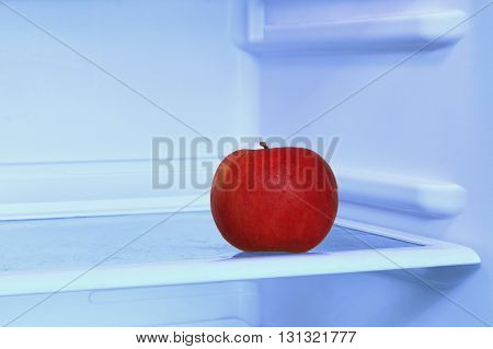 Healthy lifestyle.Red apple in domestic refrigerator taken closeup. Toned image.