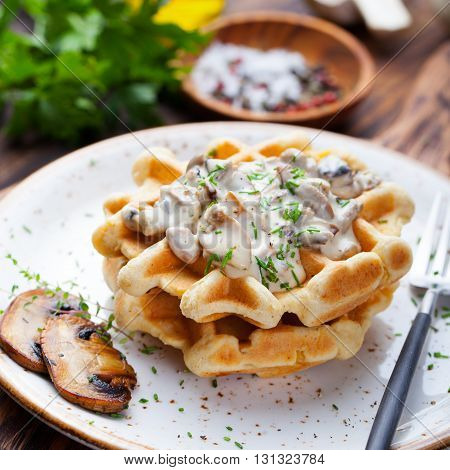 Savory waffles with corn and mushroom creamy sauce on a plate on a wooden background