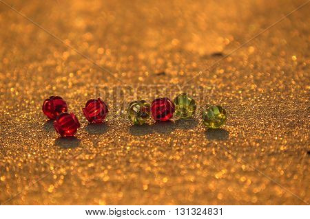 Red and green colored beads on golden sand