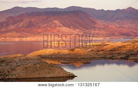 colorful desert mountain overlooking lake at sunset