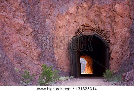 Tunnel cut in rock leading through mountain